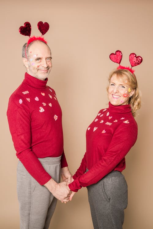 Man in Red Sweater Standing Beside Woman in Red Sweater