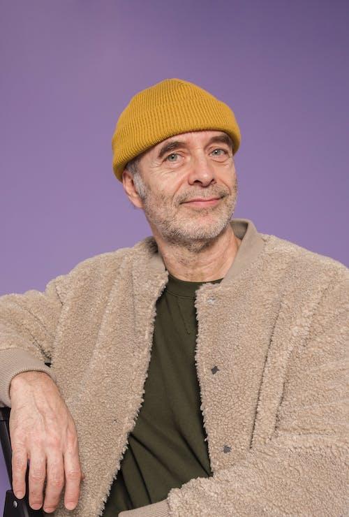 Man in Yellow Knit Cap and Brown Coat