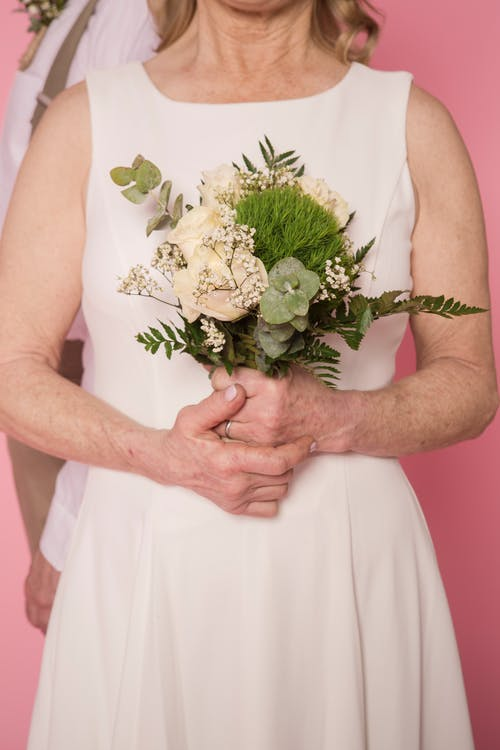 Woman in White Dress Holding White Flower Bouquet