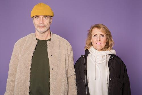 Man in Yellow Knit Cap Beside Woman in Black Jacket