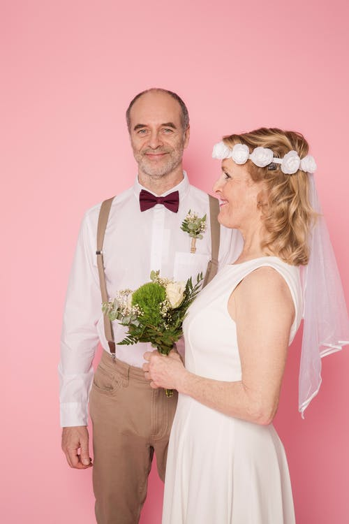 Man in White Dress Shirt and Woman in White Sleeveless Dress
