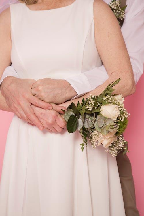 Woman in White Sleeveless Dress Holding White Flower Bouquet