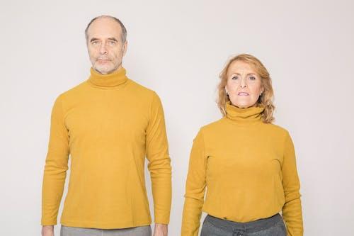 Man in Yellow Turtleneck Long Sleeve Shirt Beside Woman in Yellow Turtleneck Sweater
