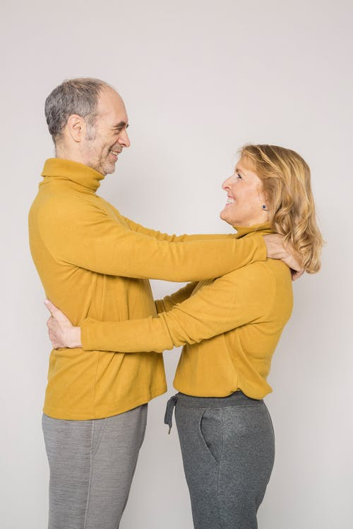 Man in Yellow Sweater Embracing Woman in Yellow Sweater