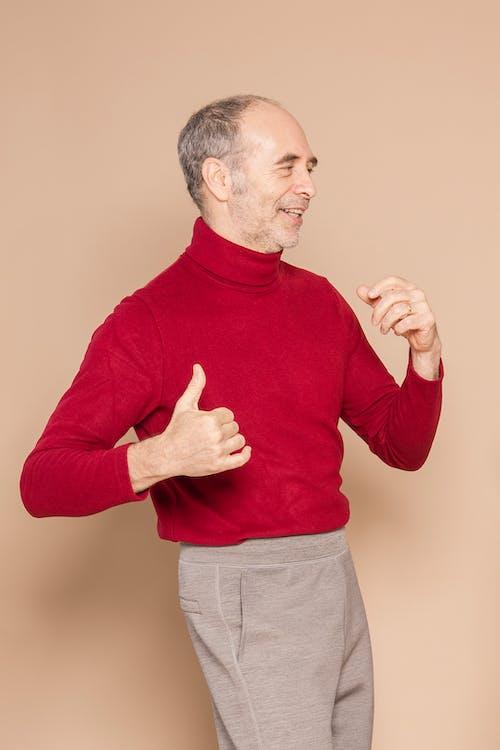 Happy mature man dancing in studio