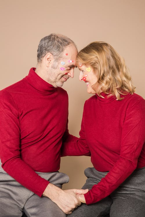 Beloved senior couple in stylish red turtlenecks with face paintings holding hands and touching foreheads while sitting against beige background in studio