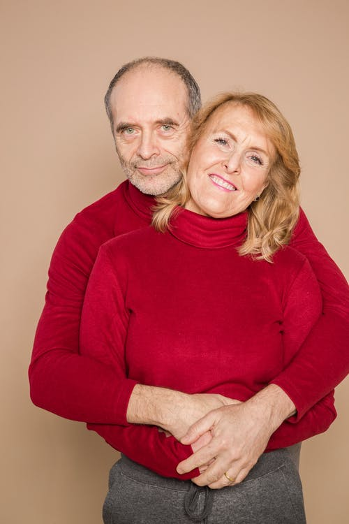 Man in Red Long Sleeve Shirt Hugging Woman in Red Long Sleeve Shirt