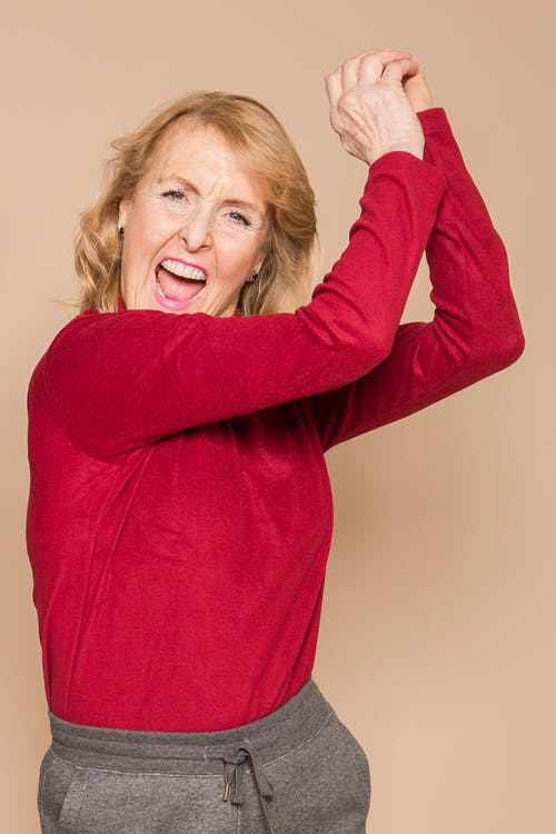 Joyful mature female with blond hair in red sweater yelling and looking at camera while dancing happily in beige studio