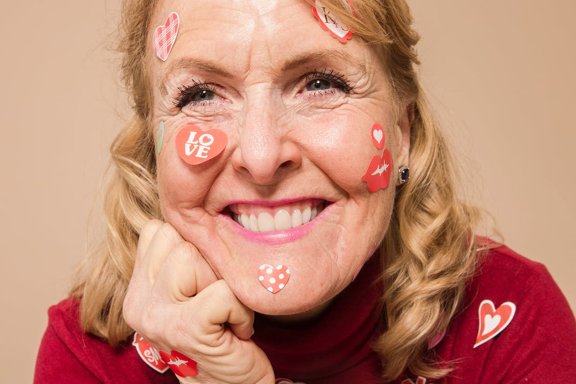 Smiling senior lady with stickers on face in beige studio