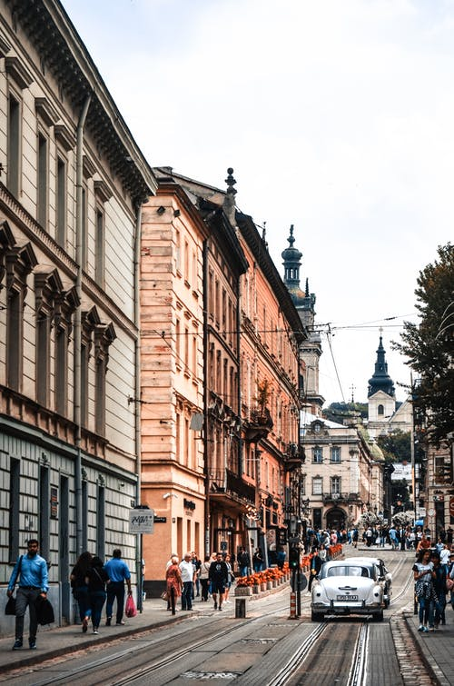 People on town street with vehicles on road near buildings