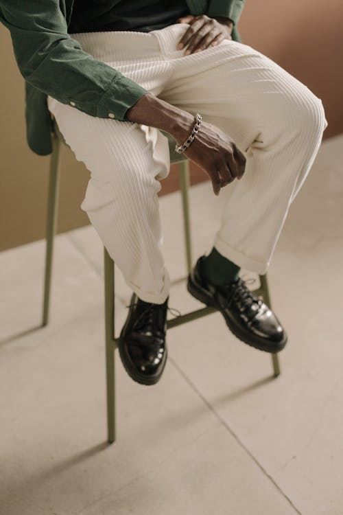 Man in White Trousers and Black Leather Boots Sitting on Chair