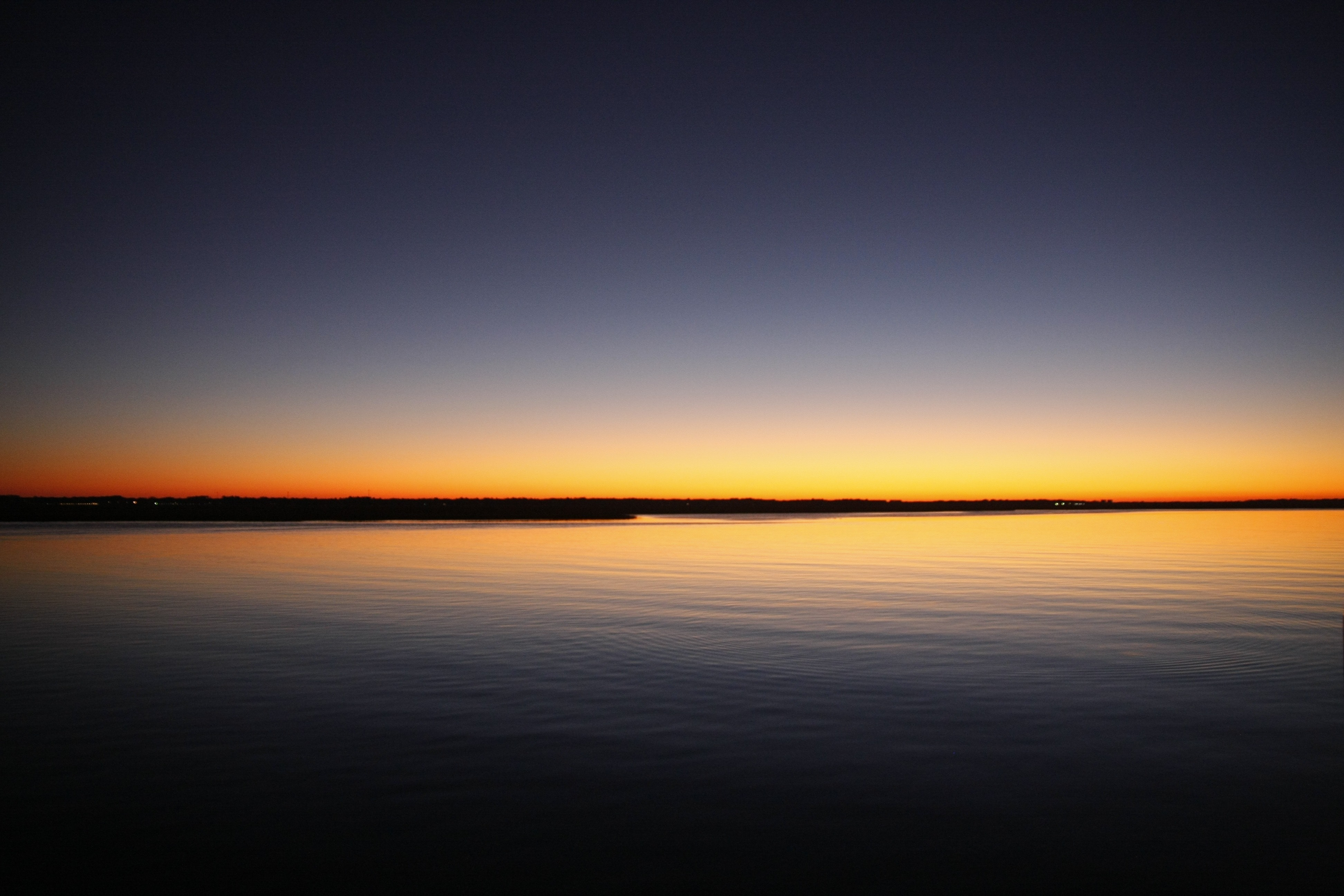 Silhouette of Calm Sea Under Blue and Orange Clear Sky ...