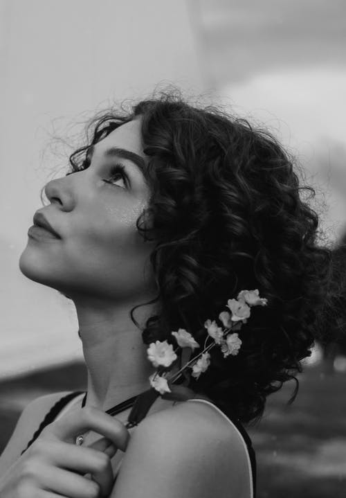 Grayscale Photo of Woman With Flower on Her Ear