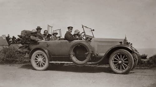 Grayscale Photo of Group Of People Sitting In A Vintage Car