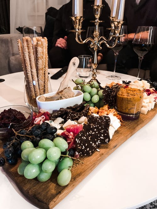 Grape with ham and cheese served on wooden board with various sauces on table with bread sticks and candlestick on room