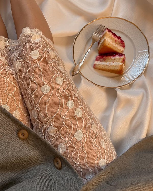 Top view of anonymous female wearing transparent cloth sitting on silk creased fabric with piece of cake on plate in room