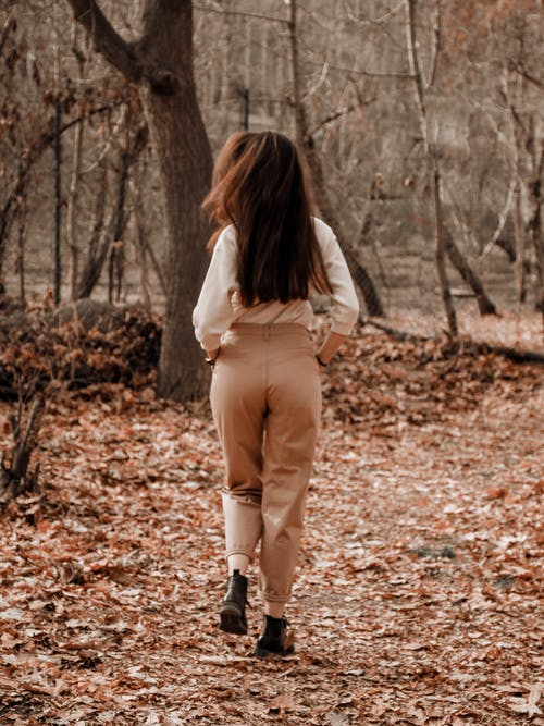 Back view of slim female model in trendy casual outfit and footwear strolling in park alone in fall in daytime