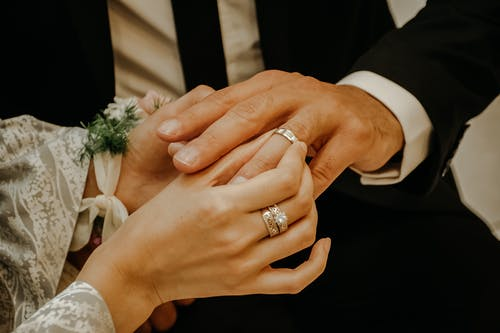 Crop anonymous bride wearing elegant white dress and jewelry golden diamond ring putting on ring on finger of groom on wedding ceremony