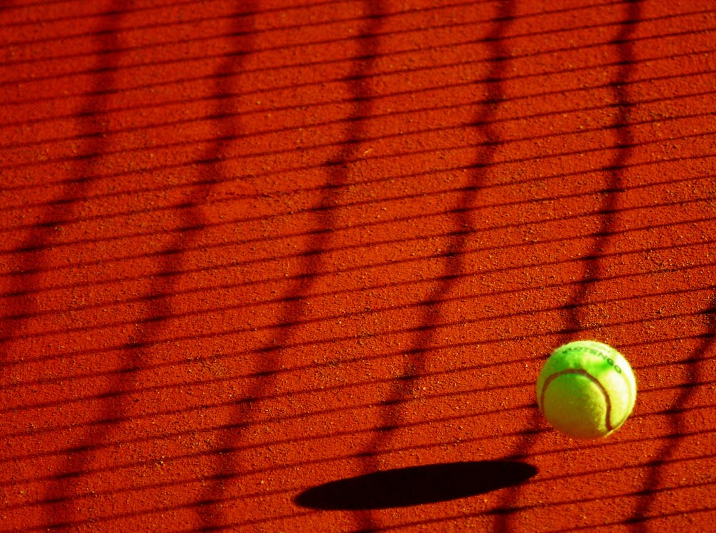 Green Tennis Ball on Red Floor during Sunny Day