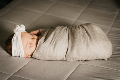 Baby in White Knit Cap Lying on Bed