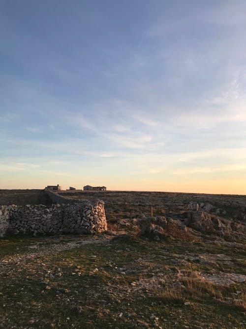 Weathered stone walls located on grassy ground with pebbles against cloudy sky and aged structures in rural area in evening time