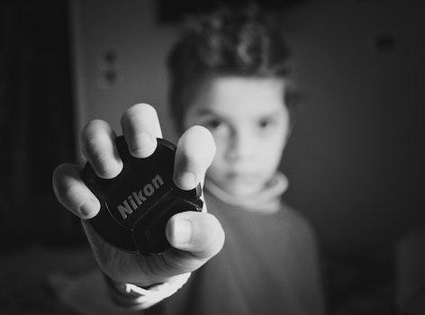 Selective Focus Photography of Boy Holding Nikon Lens Cover