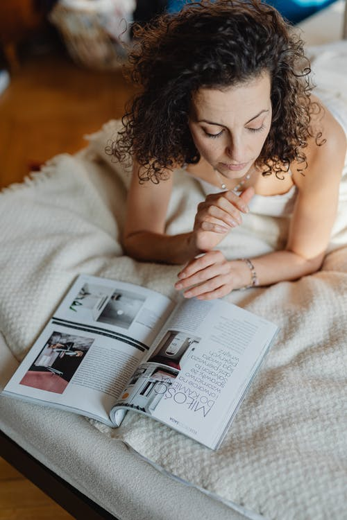 Woman Lying On Front In Bed Looking At A Magazine