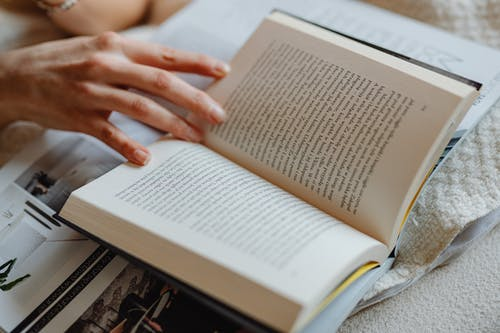 Person Holding The Pages Of An Open Book