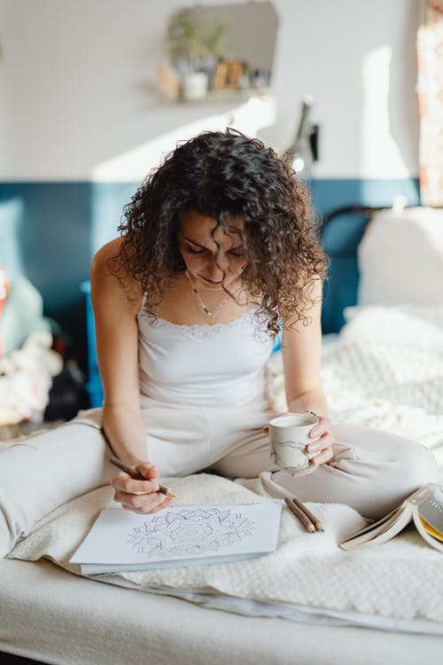 Woman in White Spaghetti Strap Top Sitting on Bed Coloring A Book