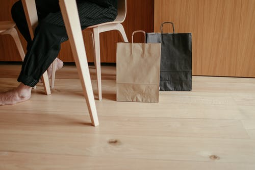 Side view of crop unrecognizable barefooted person resting on chair at table near paper bags placed on wooden floor at home