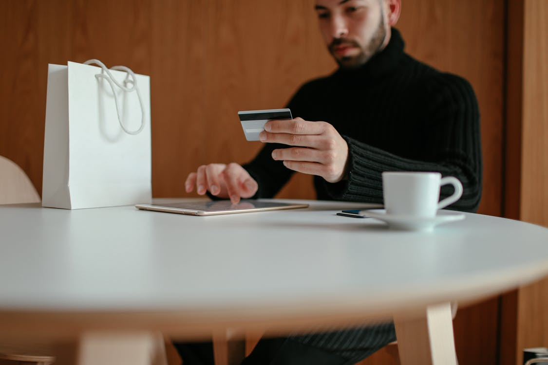 Crop focused bearded young man using tablet while doing online purchase with credit card sitting at table in modern cafe with coffee cup and shopping bag