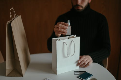 Focused man pulling out beauty product from shopping bag at table