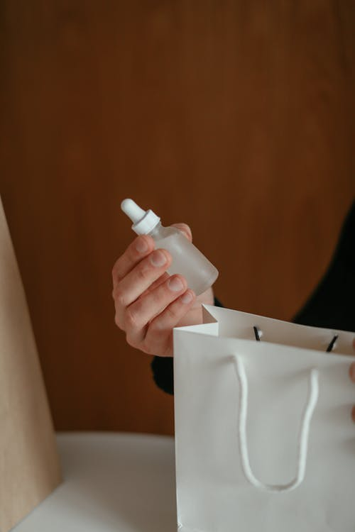 Crop faceless male buyer holding bottle of cosmetic serum sitting at table with shopping bags after receiving order