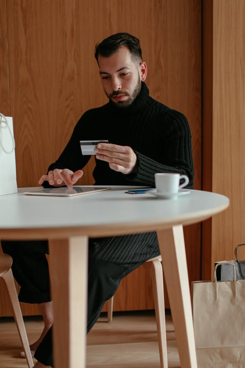 Confident young man using tablet and doing online shopping at home