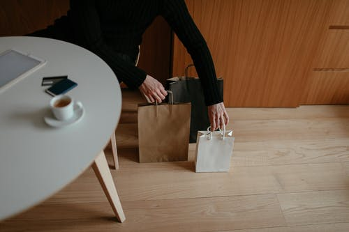 From above of crop unrecognizable male shopaholic in casual clothes sitting at table with tablet and coffee and putting paper bags on floor after shopping