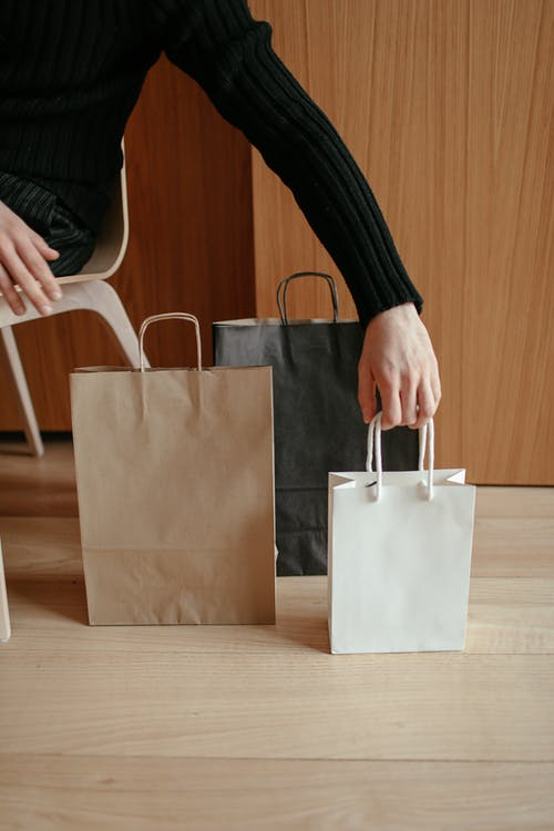 From above of crop faceless male putting various paper bags on wooden floor while sitting on chair at home after shopping