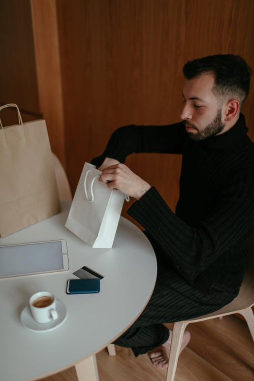 Young man drinking coffee at table and checking purchases at home