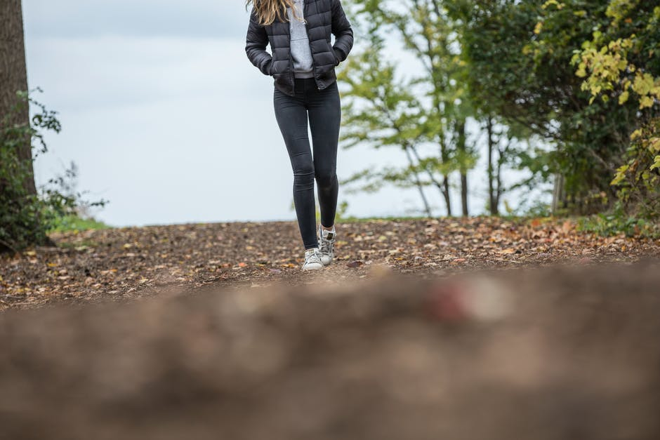 Woman in Black Leggings While Walking on Brown Road