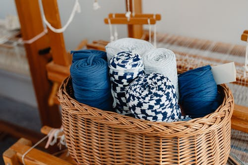 Blue and White Yarn Rolls in Brown Woven Basket
