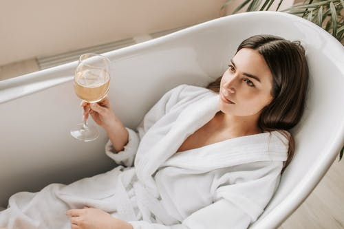 Woman in White Bathrobe Holding Clear Drinking Glass