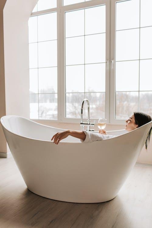 Woman in Bathtub in Front of Window