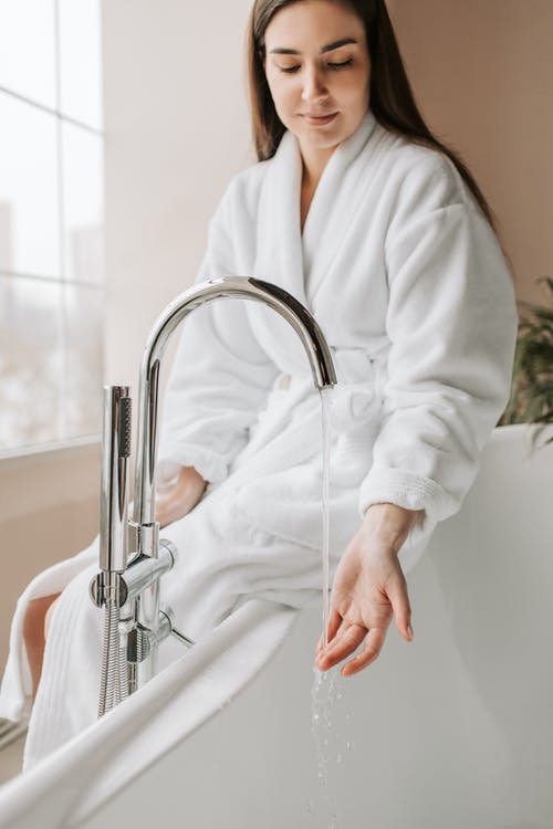 Woman in White Robe Holding Silver Faucet