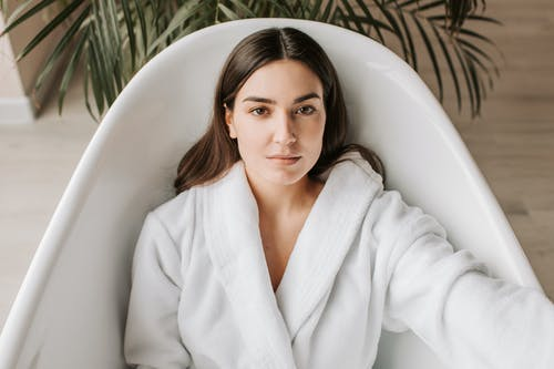 A Woman in White Bathrobe Lying in the Bathtub