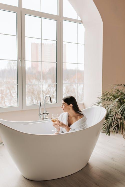 Woman in White Ceramic Bathtub Near Glass Window