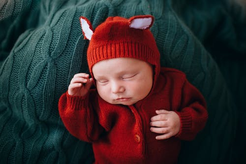 Funny cute newborn baby in knitted red woolen jumpers