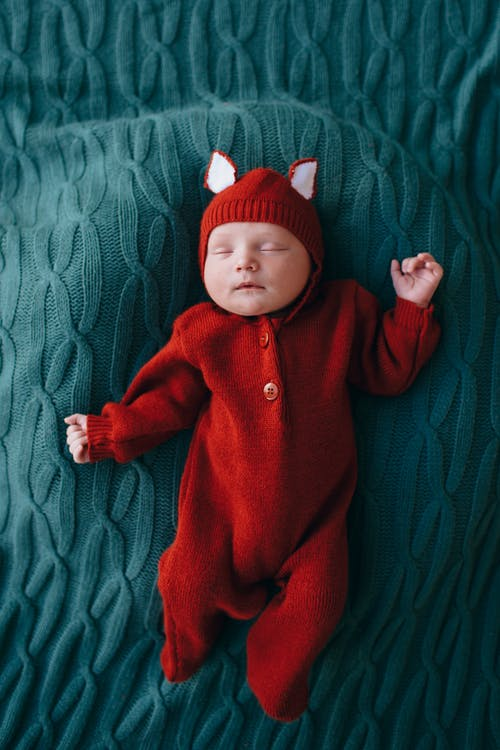 Top view of tranquil small infant in bright red costume sleeping on knitted blue blanket