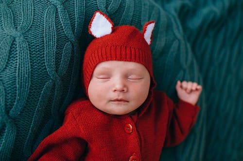 Cute little infant in red warm knitted jumpers sleeping