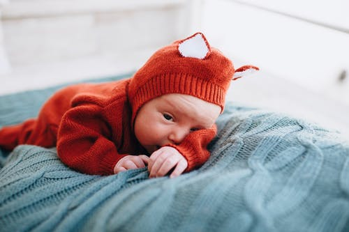 Small adorable infant in bright red woolen costume on blue soft blanket on blurred background