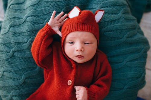 Little peaceful baby in red woolen costume