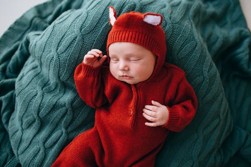 Small cute baby with gentle little hands sleeping on blanket